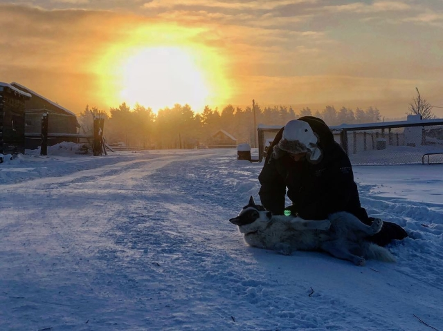 Man and dog play in freezing temperature of -62 degree celsius in Oymyakon.