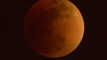 The moon turns a reddish hue as it passes through the Earth's shadow during a lunar eclipse.