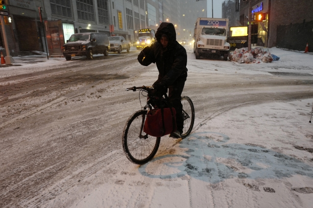 A bicyclist manoeuvres through an early morning snowfall in New York.<a></a>