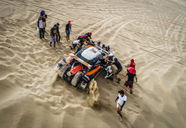 The Volvo team helps their driver as his car gets stuck in the sand.
