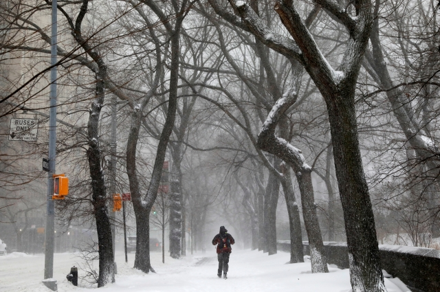 A man walks in the snow next to Central Park along 5th avenue in upper Manhattan during Storm Grayson in New York City, New York.