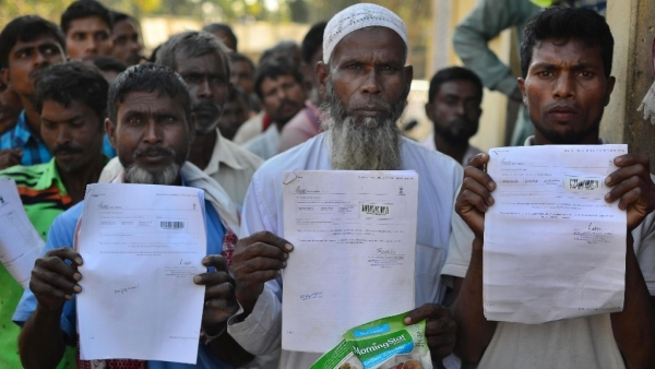 People show their acknowledgement receipts after checking their names in a draft for National Register of Citizens (NRC), in Guwahati on Monday.