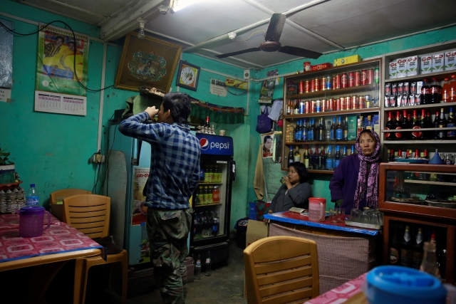 A youth drinks whiskey at a bar in the capital city of Thimphu, Bhutan, 16 December  2017.