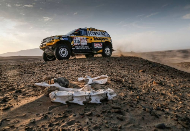 A Renault car passes through the mighty terrain.