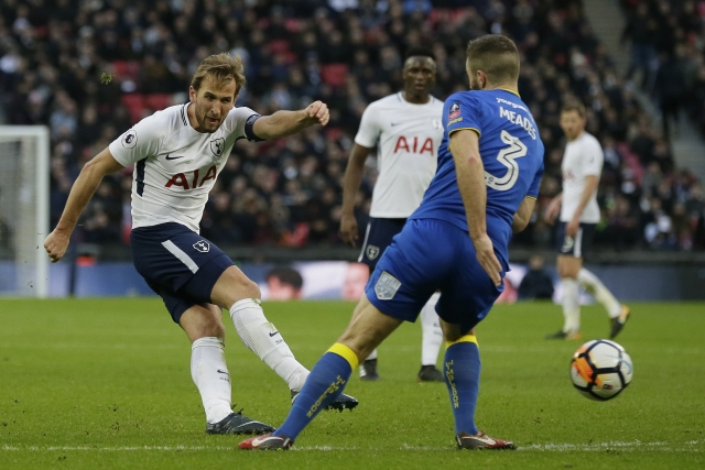 Tottenham's Harry Kane, left, shoots past Wimbledon's Jonathan Meades.