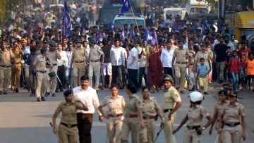 Policemen accompany protesters staging a demonstration in Mumbai on 2 January against the violence in Bhima Koregaon in Pune district.