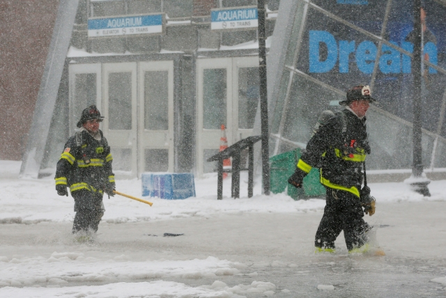 Boston firefighters wade through a street flooded from tidal surge during Storm Grayson in Boston, Massachusetts.
