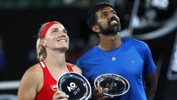 Hungary's Timea Babos ( left) and partner India's Rohan Bopanna hold their runner-up trophies at the Australian Open in Melbourne.