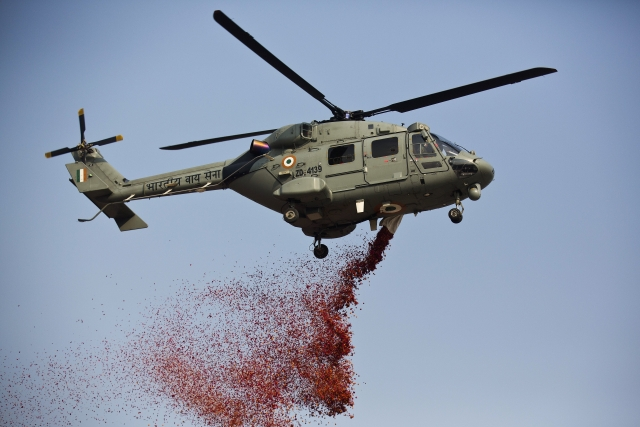 An Indian Air Force helicopter sprays flower petals during Republic Day parade in Gauhati, India, Friday, 26 January 2018.