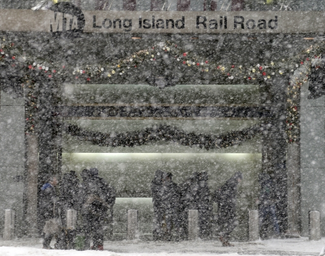 Pedestrians at the entrance of the Long Island Railroad are obscured by snow in New York.