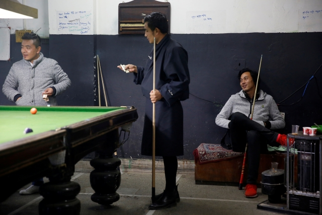 Men play snooker and gamble in a snooker hall in the capital city of Thimphu, Bhutan, 12 December 2017.