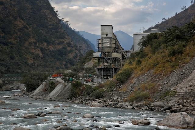 The Punatsangchu river runs past an industrial site located near the town of Wangdue Phodrang, Bhutan, 13 December  2017.