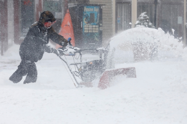 A man uses a snowblower to clear snow from a street during a snowstorm in Port Washington, New York.