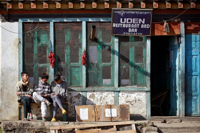 Youths sit outside a restaurant in the capital city of Thimphu, Bhutan, 16 December 2017.