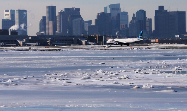 Ahead of an incoming winter snow storm, a Jet Blue flight waits to take off from Logan International Airport next to the frozen waters of the Atlantic Ocean harbour between Winthrop and Boston, Massachusetts, US.