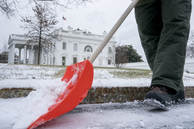 A National Park Service worker clears snow on the North side of the White House.