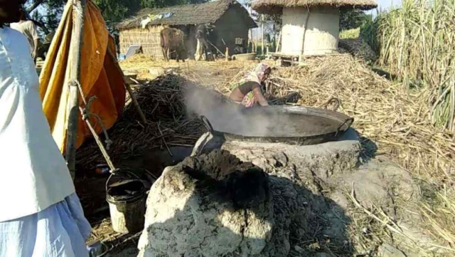 Rukhmani Devi boiling sugarcane juice to make <i>gur.</i>