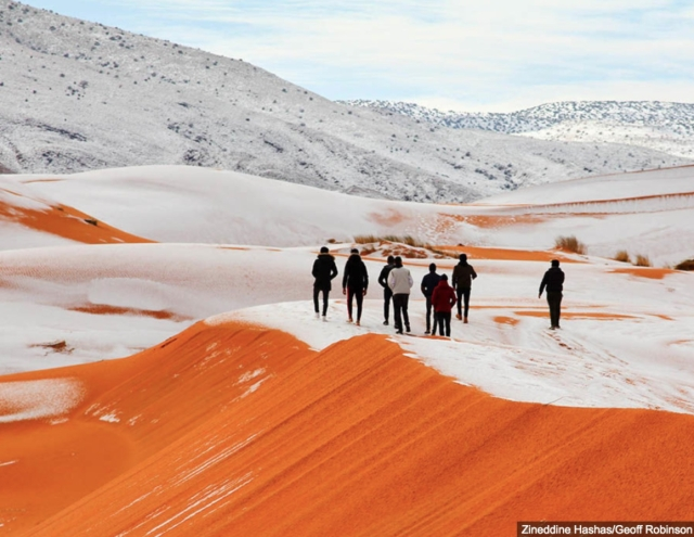 People walking on snow-capped mountains in Sahara.