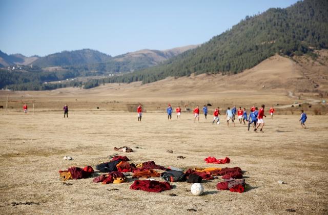 Buddhist monks play football in the Phobjikha Valley, Bhutan, 14 December  2017.