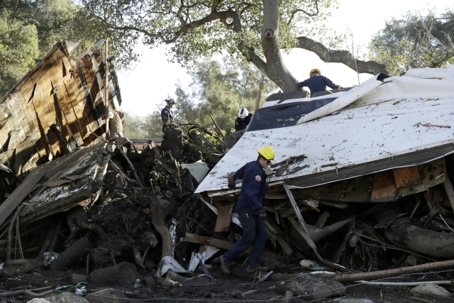 Crews work upon some of the disaster caused by the mudslides in california.