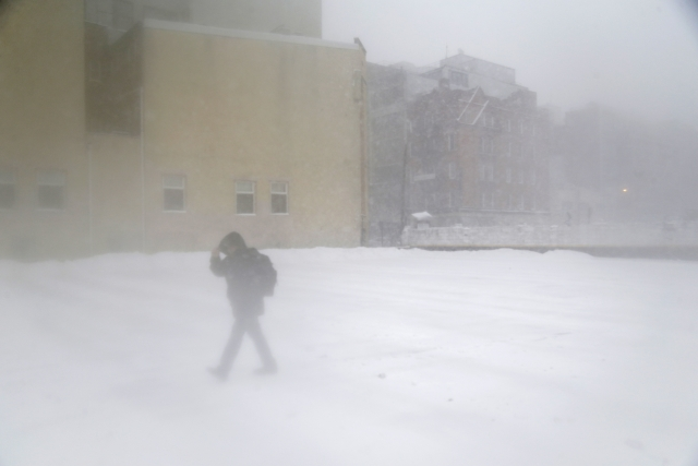 A pedestrian makes their way across an snow-blown parking lot in Hoboken, New Jersey.<a></a>
