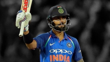 Virat Kohli raises his bat after scoring a century in an ODI against Sri Lanka in Colombo.