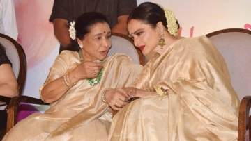 Twinning in gold, Asha Bhosle shares a moment with Rekha.