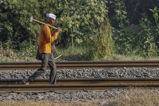 A worker carries a sledgehammer as he walks along rail tracks in Mumbai.