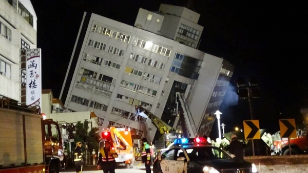 Rescuers are seen entering a building that collapsed onto its side from a 6.4 magnitude earthquake in Hualien County, eastern Taiwan.