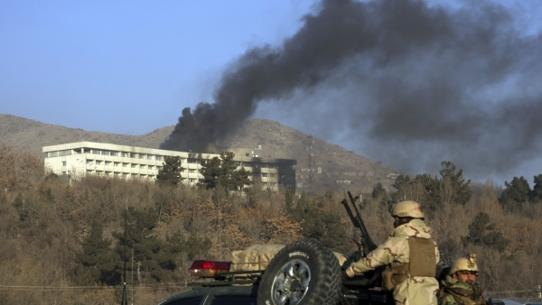 Afghan security personnel stand guard as black smoke rises from the Intercontinental Hotel after an attack in Kabul.