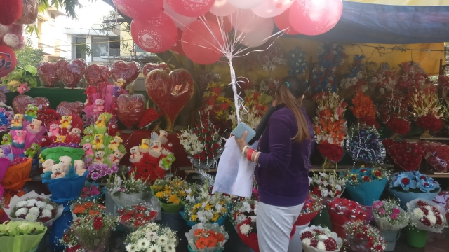 A woman choosing bouquets at Singh's shop.
