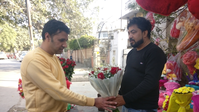 Gangadhar Singh showing a bouquet to one of his customers