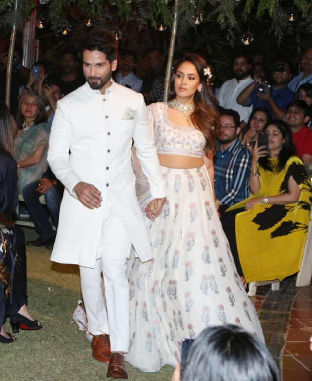 The couple walk amongst the guest in their designer wear.