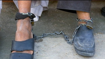 A former warlord and a Talib chained together at a mental health unit in Herat, WEstern Afghanistan.
