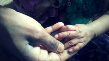 The 8-month-old who was raped by her cousin holds her mother's hand.