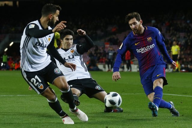 FC Barcelona's Lionel Messi, right, duels for the ball against Valencia's Carlos Soler.