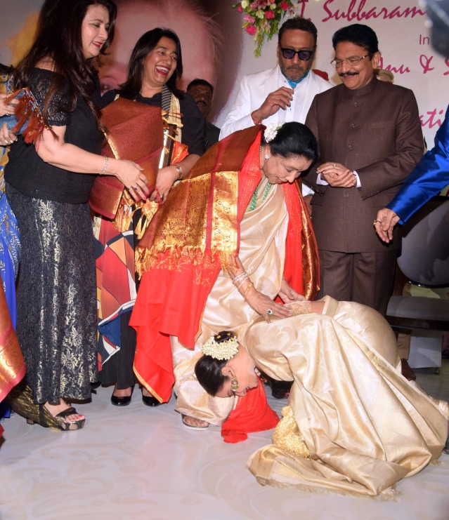 Rekha touches Asha Bhosle's feet.