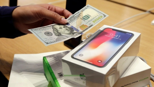 A customer hands over cash as she pays for an iPhone X at the Apple Store on New York's Fifth Avenue. Image used for representation.