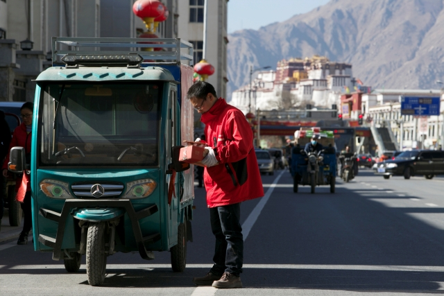 A delivery man of Alibaba's logistics unit Cainiao checks his phone as he delivers a parcel in Lhasa on 14 January  2018.