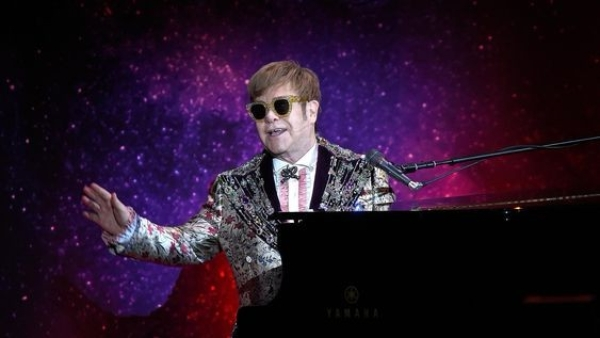 Elton John on stage, performing live.
