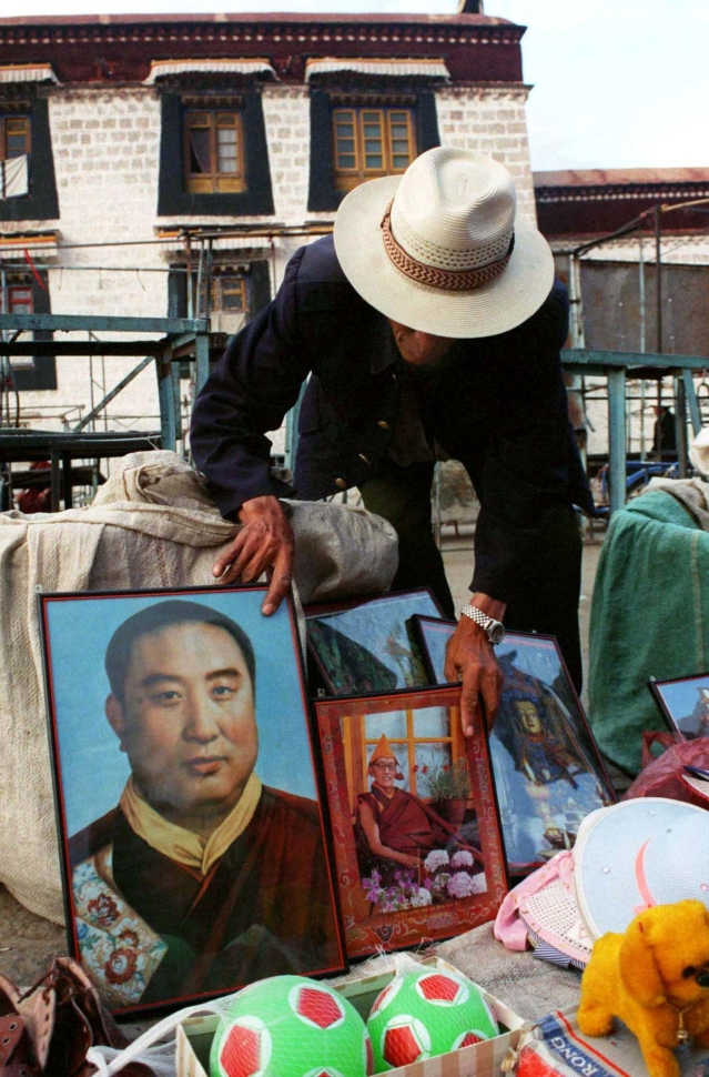 A Tibetan vendor moves a photograph of the Panchen Lama to reveal a picture of a young Dalai Lama in front of the Jokhang Temple in Lhasa on 26 May 1998.