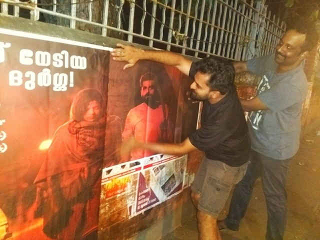Kannan Nayar in action sticking posters of <i>S Durga </i>around town<i>.</i>