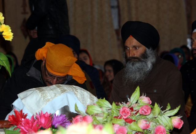 A victim's family member prays at the Gurudwara