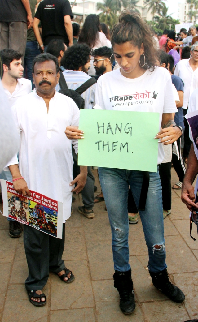 Singer Anushka Manchanda holds a sign at the protest gathering.