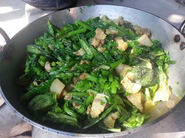 Pork being cooked with leafy vegetables in a traditional vesel