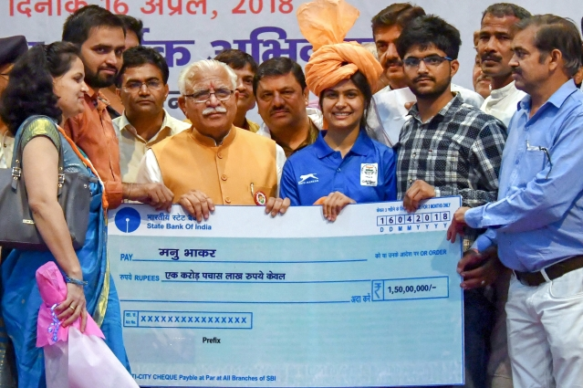 Haryana Chief Minister Manohar Lal Khattar presents a cheque worth Rs 1.5 crore to Commonwealth gold medal winner shooter Manu Bhaker, in Jhajjar on 16 April.