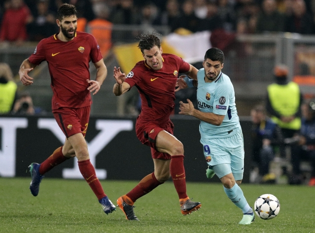 Barcelona's Luis Suarez, right, is challenged by Roma's Kevin Strootman during the Champions League.
