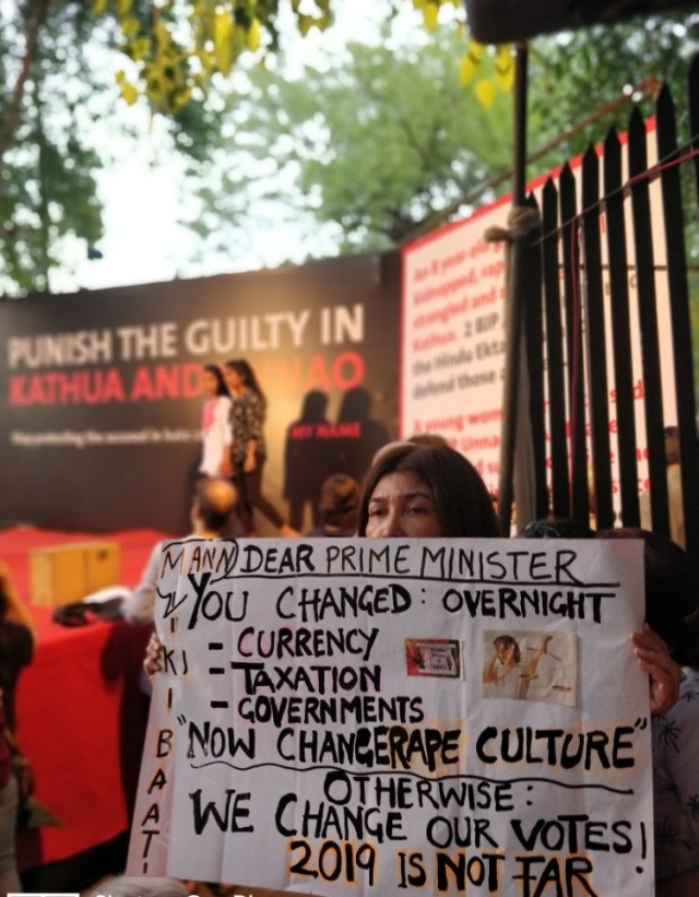 "A woman holding a placard asking the PM to take action and change the ""rape culture."""