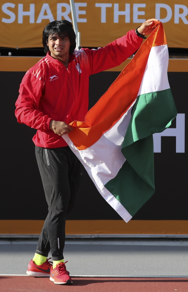 India's Neeraj Chopra holds the national flag after winning gold in the men's javelin final at Carrara Stadium during the Commonwealth Games.