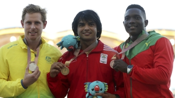 Men's javelin gold medalist India's Neeraj Chopra, centre, stands next to silver medalist Australia's Hamish Peacock, left, and bronze medalist Grenada's Anderson Peters.